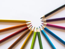 Color pencils in semi-circle on white paper Stock Photography