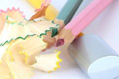Color pencils with sharpener and shavings. Close up of colorful green, pink and yellow wooden pencils with sharpener and shavings Royalty Free Stock Photo