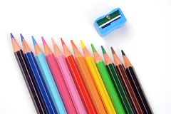 Color pencils with sharpener on white background. Color pencils regularly used by upcoming artists and various students for art work and project work Royalty Free Stock Photography