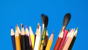 Color pencils are spinning. On a blue background stock video
