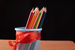 Color pencils in tin can on wood table on black background. Color pencils in tin can on wood table on black Stock Photo