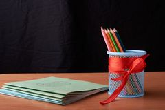 Color pencils in tin can on wood table on black background. Color pencils in tin can on wood table on black Stock Image