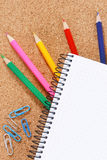 Color pencils under blank notebook Royalty Free Stock Image