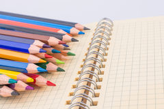 color pencils of various colors near a notebook Stock Image