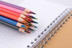 color pencils of various colors near a notebook Stock Images
