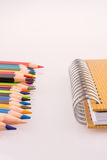 color pencils of various colors near a notebook Royalty Free Stock Image