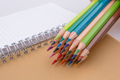 color pencils of various colors near a notebook Stock Photo