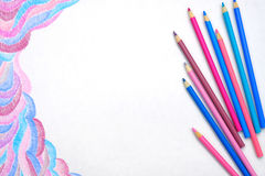 Color pencils on white background with abstract picture Royalty Free Stock Images