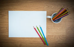 Color pencils in white coffee cup and white paper Stock Photo