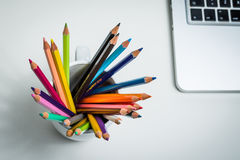 Color Pencils in a white mug and a laptop. Sharp multi color pencils in a white mug with a portable computer and a white  background Royalty Free Stock Photo