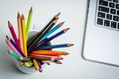 Color Pencils in a white mug and a laptop. Sharp multi color pencils in a white mug with a portable computer and a white  background Royalty Free Stock Images