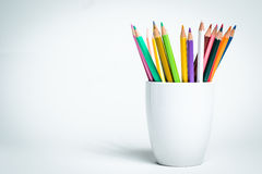 Color Pencils in a white mug. Sharp multi color pencils in a white mug and a white  background Royalty Free Stock Photography