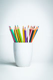 Color Pencils in a white mug. Sharp multi color pencils in a white mug and a white  background Stock Photography