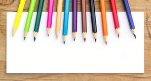 Color Pencils and white paper on wooden Royalty Free Stock Photo