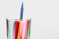 Color pens in glass with one pen higher from the others Royalty Free Stock Images