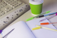 Color pens and notebook with coffee and keyboard Stock Photography