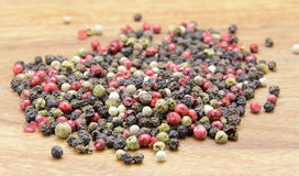 Color pepper. Pepper sprinkled on raw wood Royalty Free Stock Images
