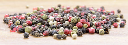 Color pepper. Pepper sprinkled on raw wood Stock Photo