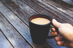 A color photo of a caucasian hand lifting a black cup of coffee from a wooden table Royalty Free Stock Image