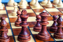 Color photo of chess Board and chess pieces, wooden chess pieces on the chessboard. Black figures in the foreground.Soft focus. Bl Royalty Free Stock Image