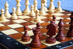 Color photo of chess Board and chess pieces, wooden chess pieces on the chessboard. Rook in the foreground. Soft focus. Blurred ba Royalty Free Stock Photography