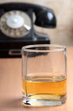Whiskey and old phone. Color photo of a glass of whiskey and old phone Stock Photos