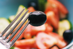 Color photo of salad vegetables on plate Fork with olive Stock Photography