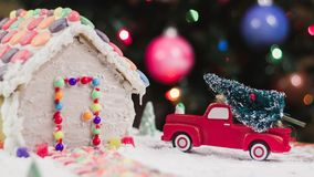 Christmas tree for the gingerbread house. Color photo of toy red truck delivering a Christmas tree in front of gingerbread house royalty free stock photos