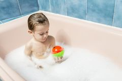 Child playing with a ball in a bubble bath. Color photography of a child playing with a ball in a bubble bath Royalty Free Stock Images