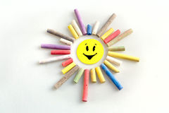 Color pieces of chalk yellow blue violet red sun on a white back Stock Photos