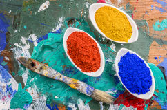 Color pigments in porcelain bowls on a wooden palette Royalty Free Stock Image