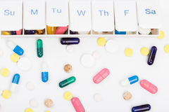 Color pills capsules and weekly pill organizer Royalty Free Stock Photos