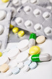 Color pills and capsuls against tablet`s packs Stock Image