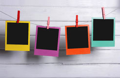Color polaroid photos hanging. With planks in background royalty free stock images
