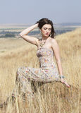 Color portrait of bohemian woman seated in golden field of grass Stock Photos