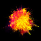 Color powder explosion paint on black background. Color powder dust explosion isolated on black background. Red and yellow fire paint coloured explode for Holi Stock Photo