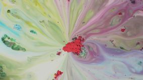 Color powder paint is mixed in water. Close-up of red powder in middle absorbs colorful washouts on surface of milk