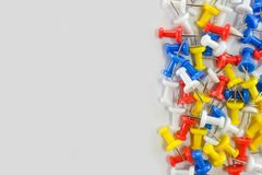 Color push pins red, yellow, white, and blue group on the right of white background royalty free stock image