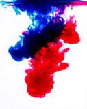 Blue and red acrylic colors in water on white. Color red blue acrylic background graphic macro royalty free illustration