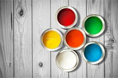 Multicolored Paint Cans on wooden background. Color red paint cans home improvement paint brush cans of paint stock image