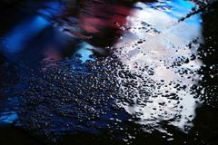 Color reflection in the asphalt after the rain in the evening Stock Photos