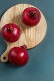 Color rojo brillante de la granada jugosa en el tablero Imagen de archivo libre de regalías