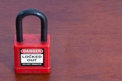 Color rojo del candado del cierre en el fondo de madera foto de archivo