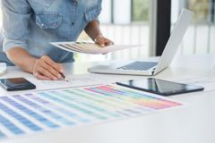 Color samples, colour chart, swatch sample, Graphic designer bei. Ng selecting Color table and graphics tablet, pen at workplace with work example on wooden desk royalty free stock photography