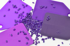 Color samples with plastic granulate. Purple color samples with polymer resin / granulate on white Royalty Free Stock Images
