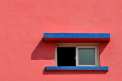 Color and shape. A small window and shadow on pink color wall, shown as geometric shape and color of the architecture Royalty Free Stock Photos