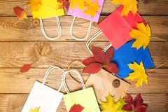 Color shopping paper bags and autumn leaves, flat lay, copy space. Autumn shopping, sales concept. Autumn holiday. Shopping in aut royalty free stock images