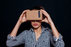 Color shot of a young woman looking through cardboard Stock Image