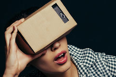 Color shot of a young woman looking through cardboard Royalty Free Stock Photo