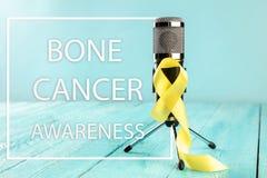 Color simbólico de la cinta amarilla para la conciencia del cáncer de hueso del sarcoma y la prevención del suicidio imagenes de archivo